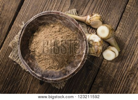 Galangal Powder(detailed close-up shot) on an old wooden table