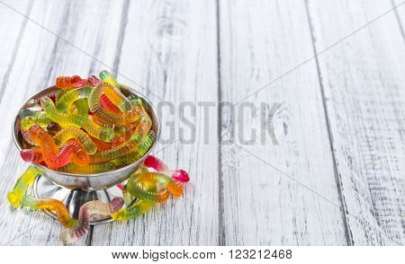 Gummi Candy (worms) on wooden background (selective focus)