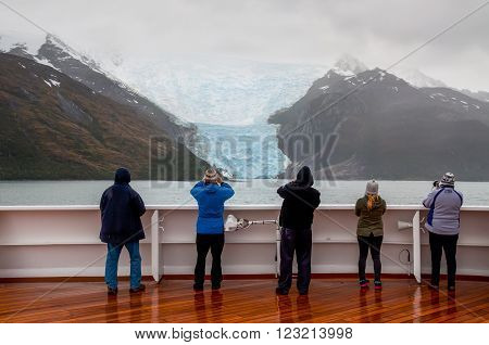 Glacier Alley, Beagle Channel, Chile - December 10, 2012: Passengers on board the cruise ship Veendam viewing beautiful Italia Glacier on Glacier Alley. Taken on a overcast rainy day. Glacier alley is also of historical importance as it was described in d