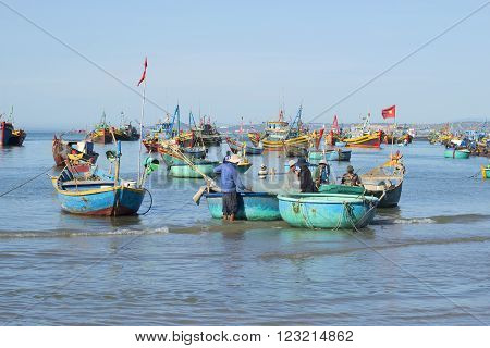 MUI NE, VIETNAM - DECEMBER 25, 2015: The fishermen in the fishing harbour. Fishermen returned from sea with the catch of fish