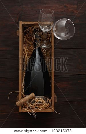 Bottle of red wine in wooden crate filled with straw next to to empty glasses with corkscrew on wooden table. Flat lay, above view, copy space,Chiaroscuro styled