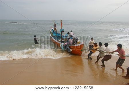 MARAVANTHE, KARNATKA/INDIA - MAY 25 2014:  Fishermen join together to pull their boat into the shore after arriving  with the catch May 25, 2014 in Marvanthe, Karnataka, India.