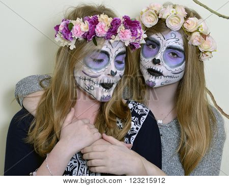Halloween two blonde girls with makeup Mexican death mask and with a wreath of flowers