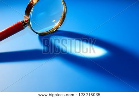 Magnifying glass with long shadow on blue background