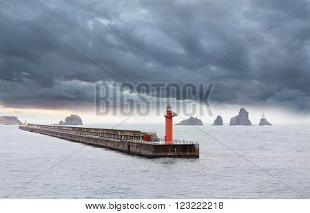 The image of a beacon on a concrete breakwater in storm weather.