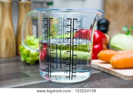 600ml / 6dl Of Water In A Measuring Cup On A Kitchen Counter With Vegetables