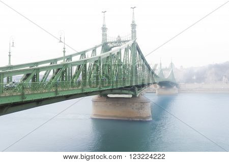 Liberty bridge over Danube river in morning fog. Budapest Hungary Europe.