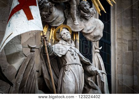 Close up view on one of statues at St Stephens Cathedral in Vienna Austria. Saint holding flag with red cross. Europe travel.