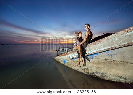 Young laughing couple is sitting on the sunken ship on the tropical sunset background.