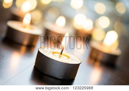 Golden Romantic Tealights In Bright Christmas Atmosphere On Wooden Table With Bokeh - Crooked Angle