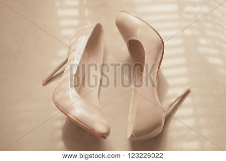 Beige wedding patent leather shoes on light background
