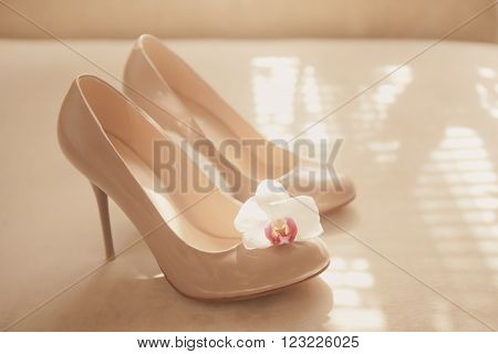 Beige wedding patent leather shoes on light background with orhid flower