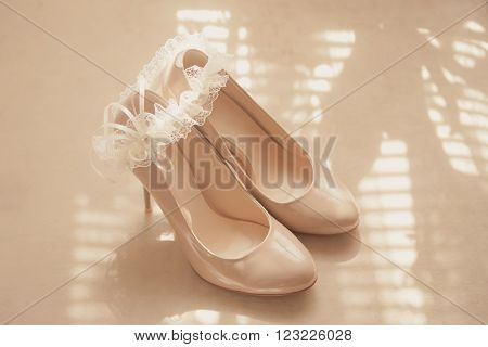 Beige wedding patent leather shoes on light background with bride garter