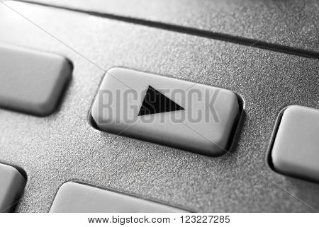 Macro Of A Grey Play Button On Chrome Remote Control For A Hifi Stereo Audio System