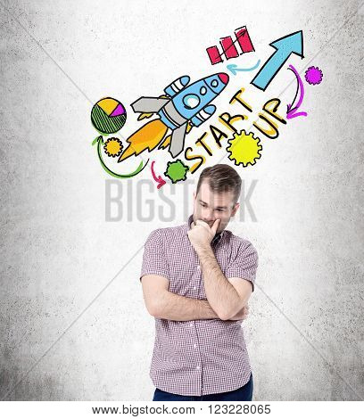Businessman with hand on chin thinking startup pictures over his head. Concrete background. Concept of start up.