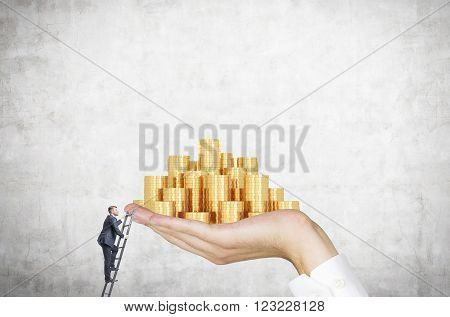 Businessman on ladder trying to reach hand with golden coins. Concrete background. Concept of career growth.