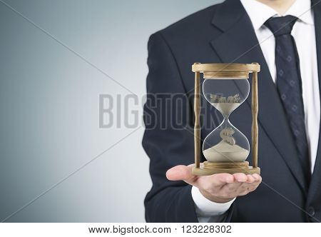 Businessman holding sand glass on palm. Sand running dollar sign down. Grey background. Concept of time.