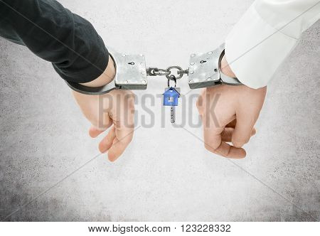 Hands of different men locked in handcuffs key to them in between. Concrete background. Concept of crime companions.