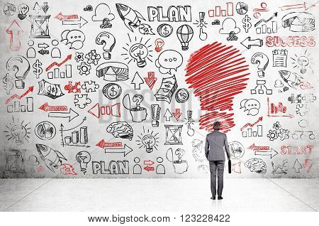 Businessman with case standing in front of concrete wall with many business icons red bulb in front. Back view. Concept of having new idea.