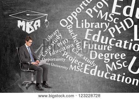 Businessman with laptop sitting on chair MBA sign above education words from laptop. Black background. Concept of searching information.