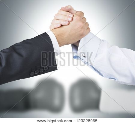 Two raised shaking hands two blurred hands in boxer gloves at background. Concept of double game.