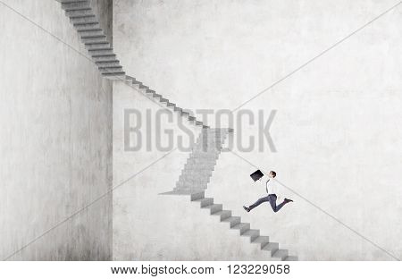 Businessman with case running up steep stairs. Concrete background. Concept of career growth.