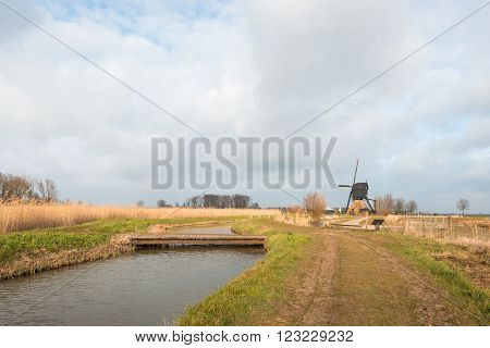 Colorful polder landscape in the Netherlands with a simple bridge in the foreground and an historic wooden post mill in the background.
