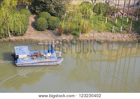 Shanghai,China 03/28/16 Chinese garbage boat with a worker cleaning a river and the chinese slogan Construction of ecological homes in chinese characters an attempt to clean the environment