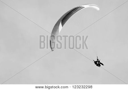 Paragliding in mountains in spring time. Blank space for a text. Black and white picture. Men on the right side. Georgia, Gudauri. ** Note: Soft Focus at 100%, best at smaller sizes