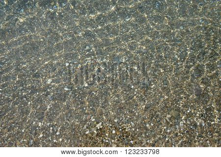 Shimmering sun glares on pebble seabed under clear water of shallow of sea beach as natural background.