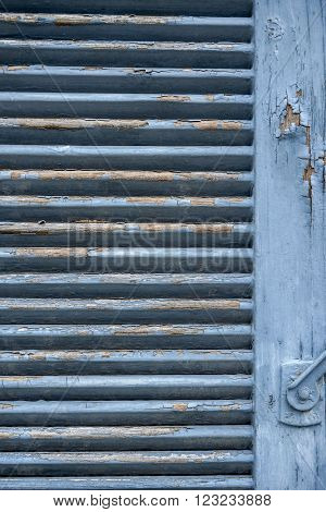 detail of a old rundown blue wooden folding shutter with blue flaking paint