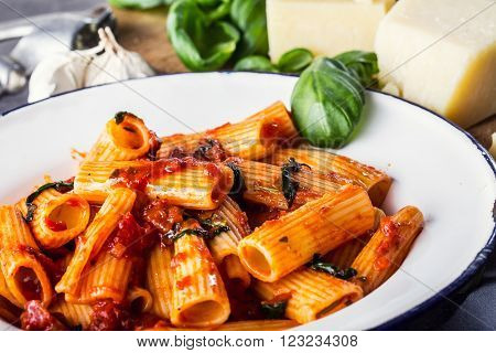 Italian and Mediterranean cuisine. Pasta Rigatoni with tomato sauce basil leaves garlic and Parmesan cheese. An old home kitchen with old kitchen utensils. ** Note: Shallow depth of field