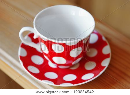 Red cup with white circles on wooden tabletop