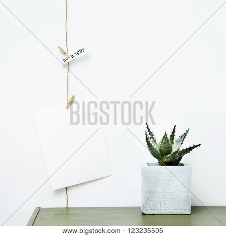 Mock up. Simple garland with poster and succulent growing on concrete pot. Hipster scandinavian home interior decoration. With place for text.