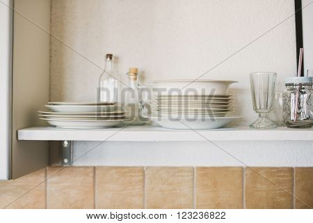 White shelf with plates glasses and jars