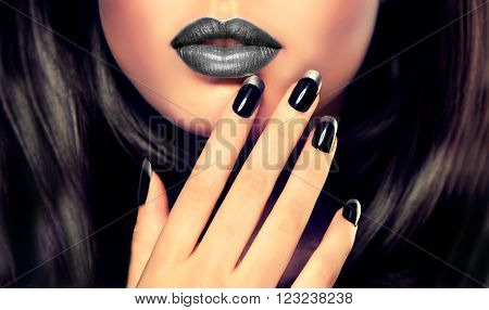 Beautiful girl showing black manicure nails, makeup, cosmetics  and manicure nails.