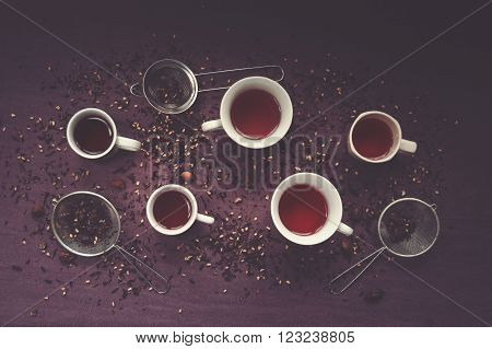 Many cups of forest fruit flavor tea, dry fruit and strainers on purple cloth.