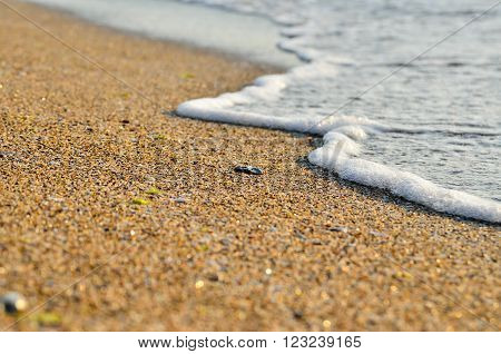 Tidal wave on a clean sandy sea beach