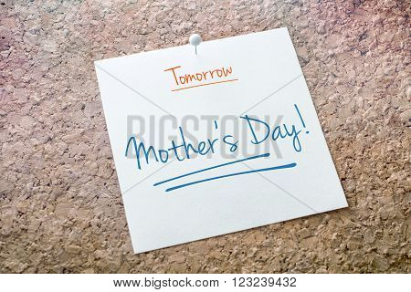 Mother's Day Reminder For Tomorrow On Paper Pinned On Cork Board