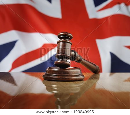 Mahogany wooden gavel on glossy wooden table. Flag of United Kingdom in the background.