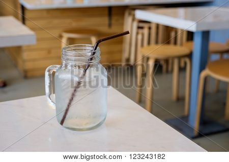 Drinking water in retro glass jar (Mason Jar) on table in restaurant.