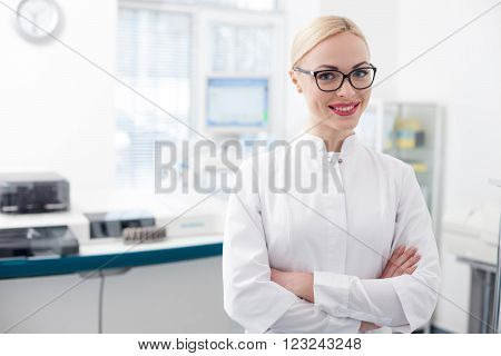 Waist up portrait of cheerful young laboratory technician is working in lab. She is standing and smiling. The woman is looking at the camera with confidence