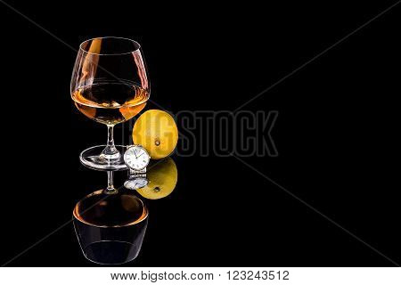 Goblet of Brandy and wrist watch with lemon on the black background