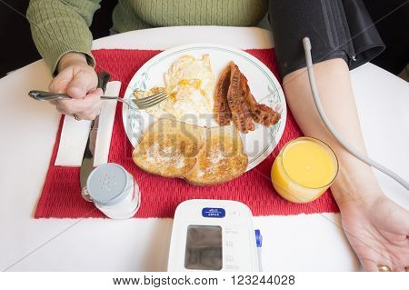 A woman eats a high cholesterol and fatty breakfast consisting of fried eggs, bacon, buttered toast, and orange juice with a salt shaker on the side while monitoring her blood pressure.