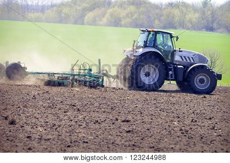 Tractor On Big Wheels On Ploughed Field Against Green Field