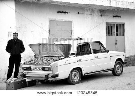 BAKU, AZERBAIJAN - DECEMBER 22 2013  Man in Baku, capital of Azerbaijan, sells oranges from the trunk of his car. A fruit seller bring produce from the countryside into Baku, the capital city of Azerbaijan.