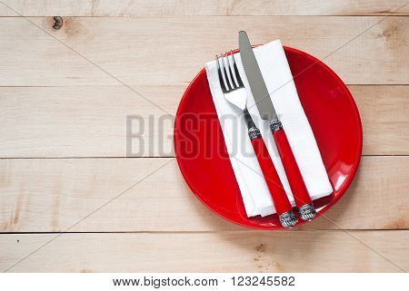 Table setting with a plate cutlery and napkin in red and white colors. View from above with copy space