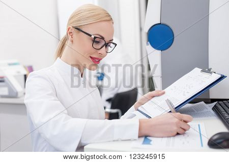 Skillful female researcher is writing report of her research in laboratory. She is sitting at the desk and smiling