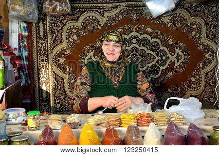 BAKU, AZERBAIJAN - JANUARY 14 2014 Lady with gold teeth selling spices in front of carpet at market in Baku, capital of Azerbaijan