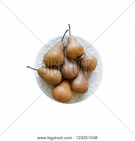 Pears on white plate on wood table isolated on white.